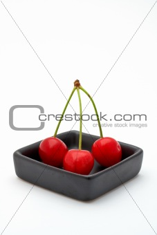 Three cherries in a black bowl