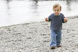 baby boy on empty pebble beach
