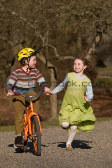 boy on bike, girl running beside him