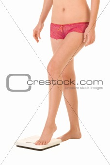 Female legs and torso stepping on bathroom scales