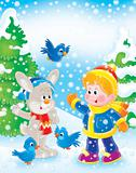 Boy, rabbit and birds in winter forest