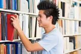 University student selecting book from library shelf