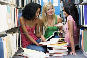 Three students working together in library
