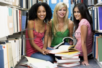 Three students working in university library