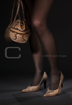 long legs in snakeskin shoes with handbag