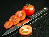 Tomatoes with vegetable knife, on black granite surface