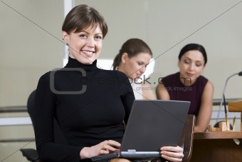 Portrait of smiling woman with the laptop on her knees