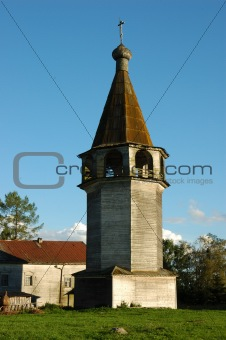 Ancient wooden country belfry at sunset