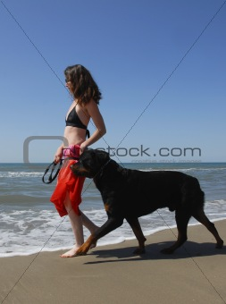 woman and rottweiler on the beach
