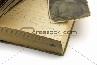An old diary that is open with a old war photo on top