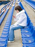 Woman with phone at stadium