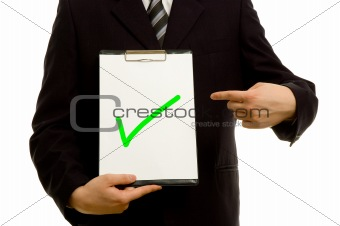 Green tick on clipboard in the hand of a businessman