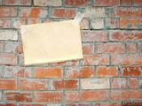Sheet of a paper, hanging on a brick wall