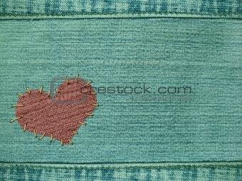 Background the heart attached by threads to jeans