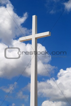 A huge religious cross being repaired with a beautiful partly cloudy day