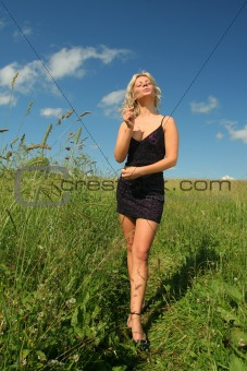 Beautifull girl in fancy black dress stands in meadow