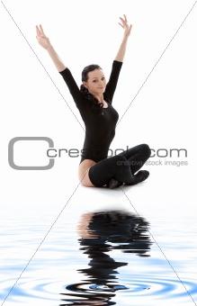 fitness in black leotard on white sand