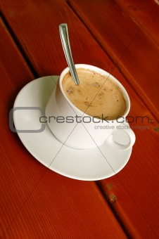 Cappuccino cup with spoon inside