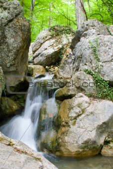 Waterfall in rocks in green relic forest