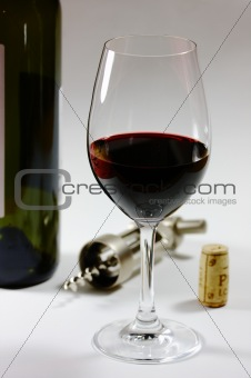 a glas of red wine and a wine bottle, the cork and the corkscrew