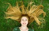 Girl with beautiful hair laying in the grass