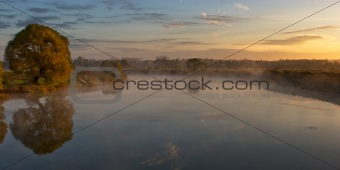 Autumn rural sunrise with tree and river