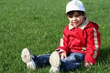 little girl in the park sitting on green grass