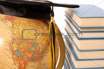 Antique globe, graduation cap and books