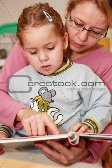 Mother and her daughter reading together