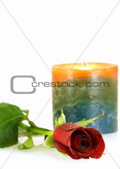 single red rose with droplets and burning candle