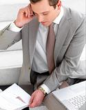 Young business man talking on phone over paperwork