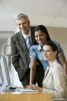 Group of business people standing by computer