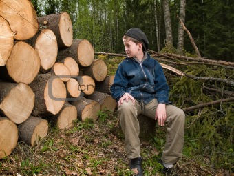 boy sitting near the prepared logs