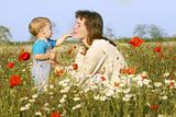 mother and son playing in flowers