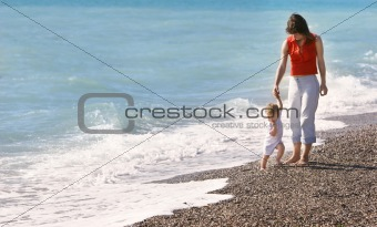 mother and son walkking on beach