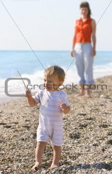 baby and mother on pebble beach