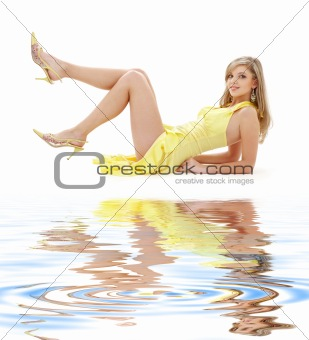 laying girl in yellow dress on white sand
