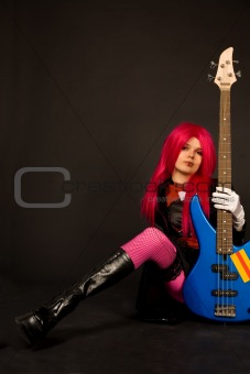 Rock girl sitting with bass guitar