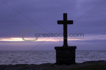 Stone cross in front of the sea