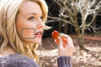 Beautiful woman eating strawberries