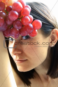 Beautiful young woman with red grape