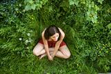 The girl with dark hair sits on a green grass