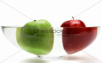 Green and red apples in vase with water