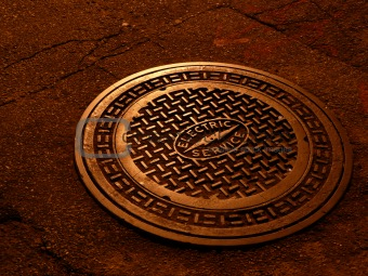 And electric service manhole cover shinning in soft copper tone under the street lights at night