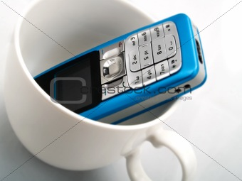 A mobile phone in a white cup
