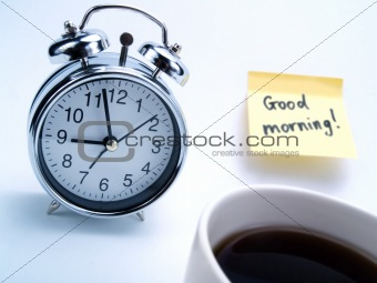 Alarm clock, cup of coffee and yellow note
