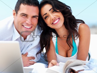 Happy young couple holding book