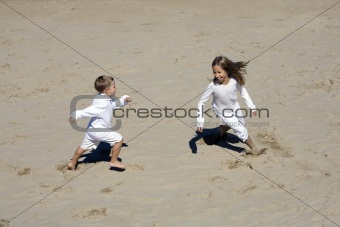 Boy and girl play together at the beach