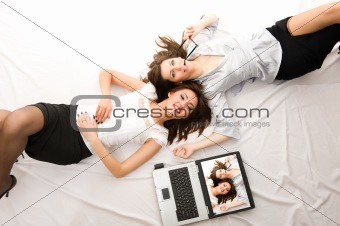 Two Young girls relax with laptop lying on the floor
