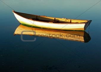Cape Cod row boat reflected at its mooring.